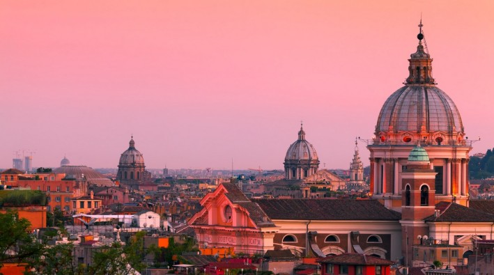 Rome skyline at dusk. In the foreground San Carlo al Corso Church.