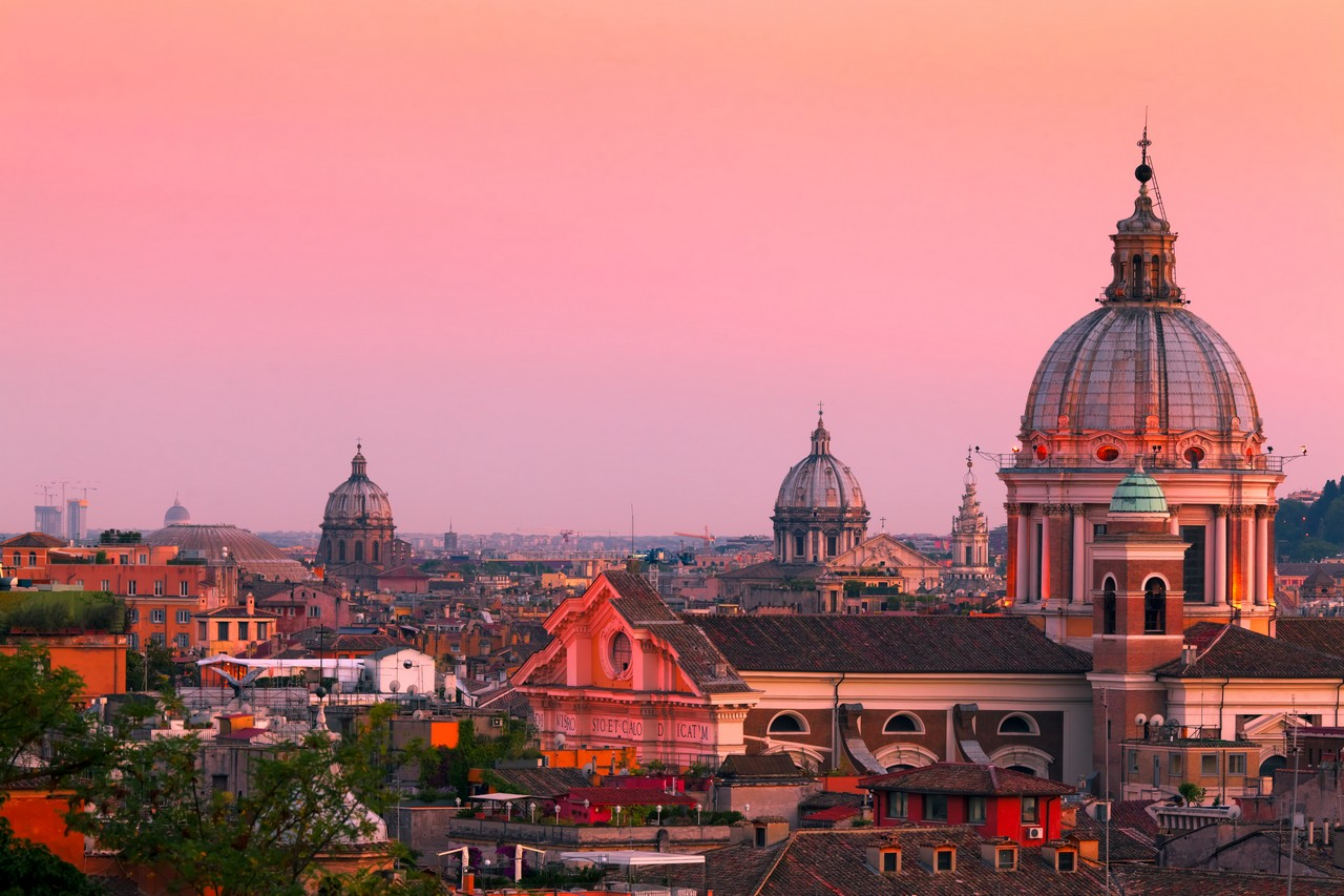 Rome skyline at dusk. In the foreground San Carlo al Corso Church.