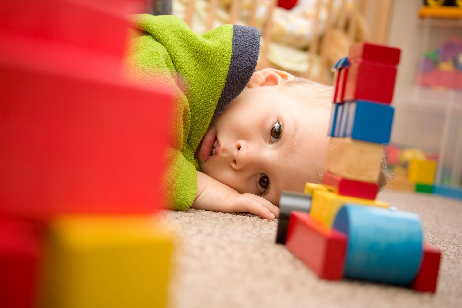 4783465 - sick boy is among the toys on the floor.