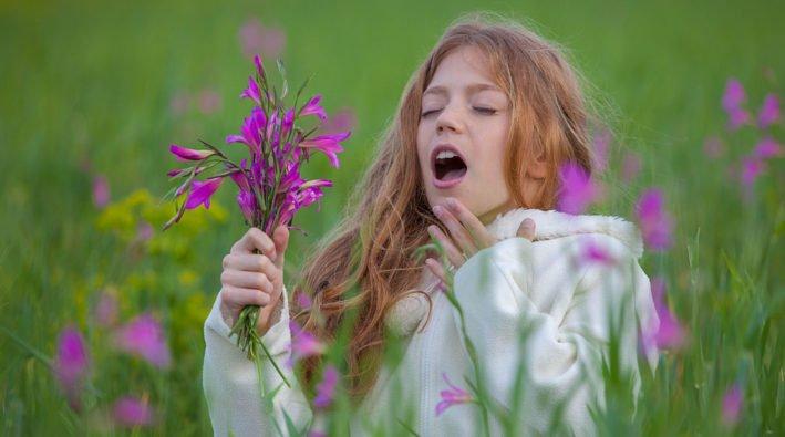 55301961 - child sneezing allergic to flower pollen in summer